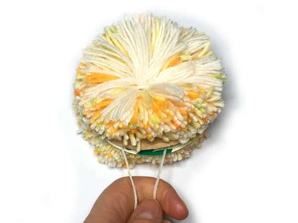 Pompon basteln: Mit Wolle zubinden